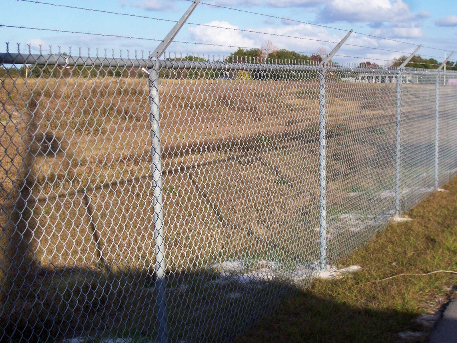 Chain link fence line post with top barbed wire arms